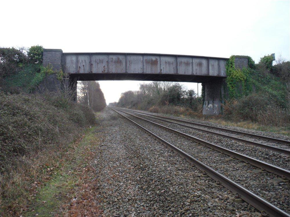 A single span brick overbridge over railway line.