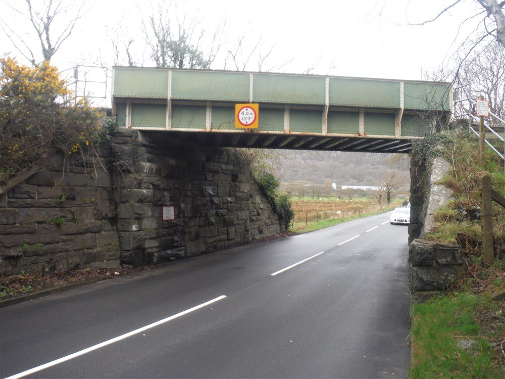 A small metal footbridge over a two lane road.