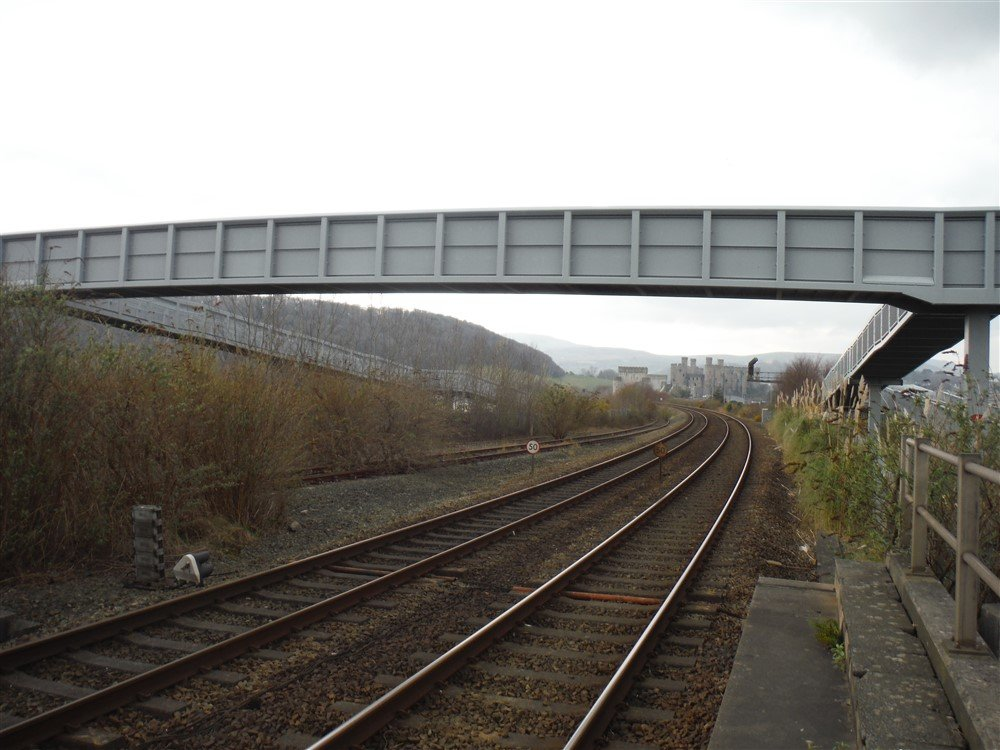 A large concrete footbridge across a railway line in the countryside.